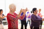Beautiful senior woman snaps her fingers as she learns new dance moves during dance class at her senior center. People are dancing in the background.
